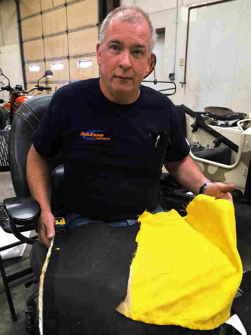 David Turbyfill holds a firefighter's shirt after testing a fireproof fabric he found on the Internet.
