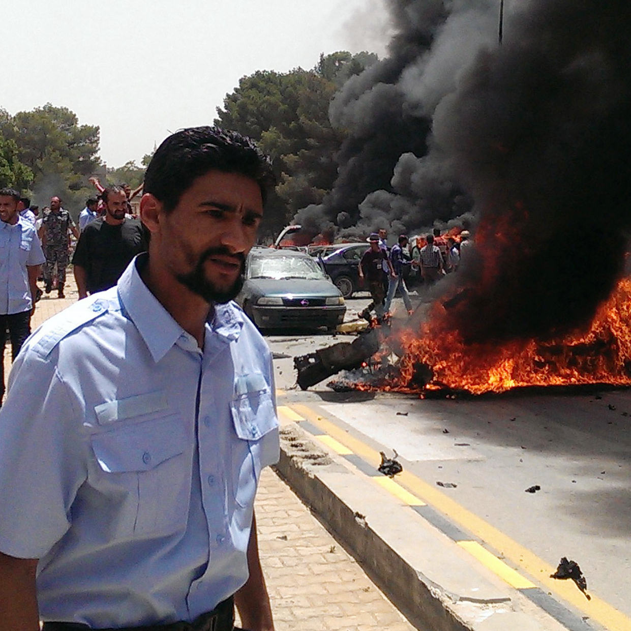 People stand near a burning car that exploded outside the parliament building, where members were drafting the new Libyan constitution, on Thursday. There were no casualties, but the blast was part of the ongoing violence in the country.