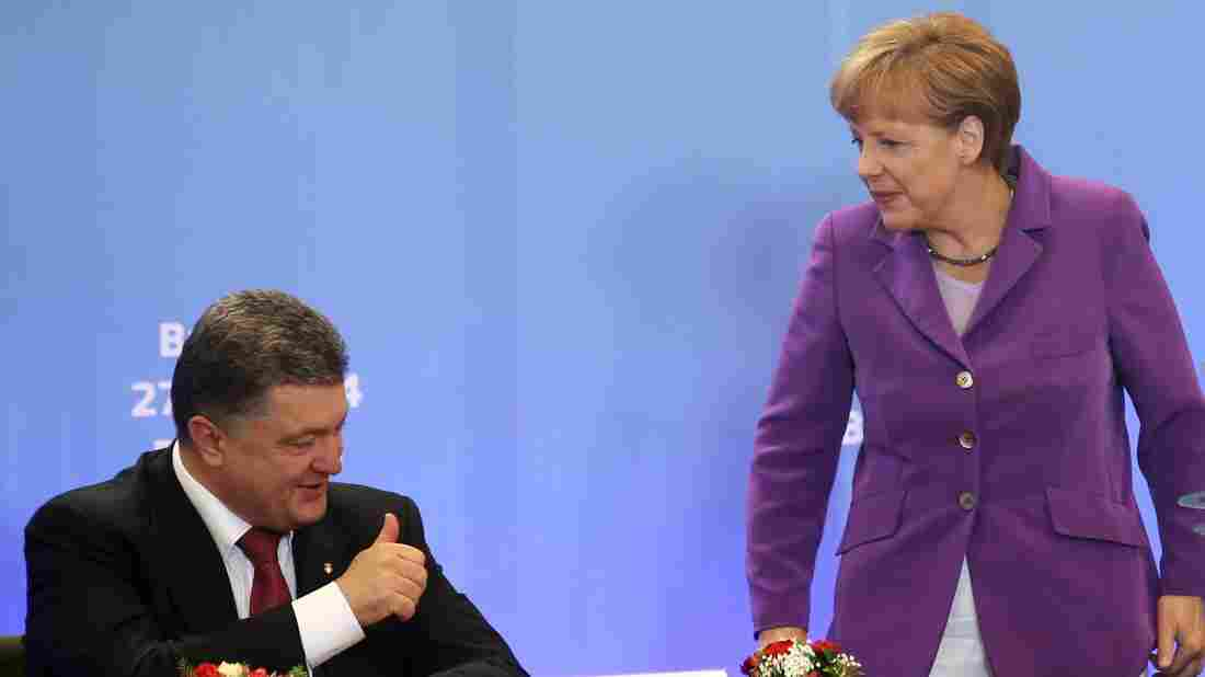 German Chancellor Angela Merkel speaks with Ukrainian President Petro Poroshenko, who signed a new economic deal with the EU at the organization's summit meetings Friday.