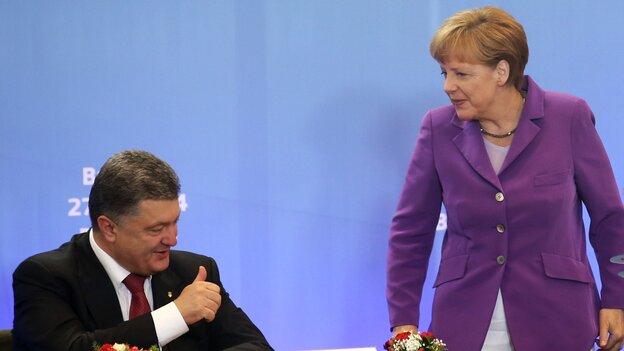 German Chancellor Angela Merkel speaks with Ukrainian President Petro Poroshenko, who signed a new economic deal with the EU at the organ