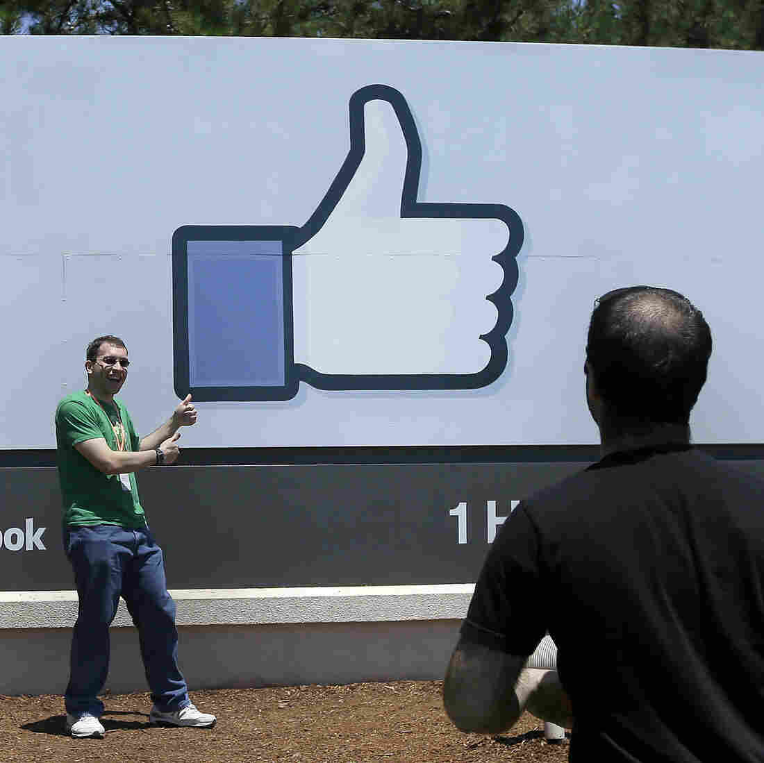 A man poses for photographs in front of the Facebook sign on the Facebook campus in Menlo Park, Calif.