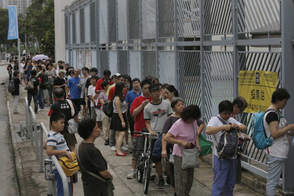 People queue at a polling center to vote in an unofficial referendum on democratic reform in Hong Kong on Sunday, June 22, 2014. (Vincent Yu/AP)