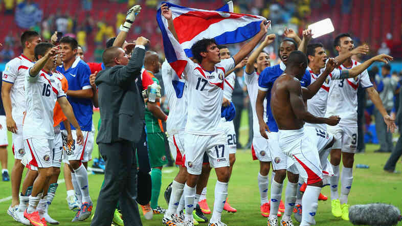 Yeltsin Tejeda of Costa Rica holds up his country's flag in celebration with his teammates after defeating Greece in a penalty shootout during the 2014 FIFA World Cup Brazil Round of 16 match on Sunday.
