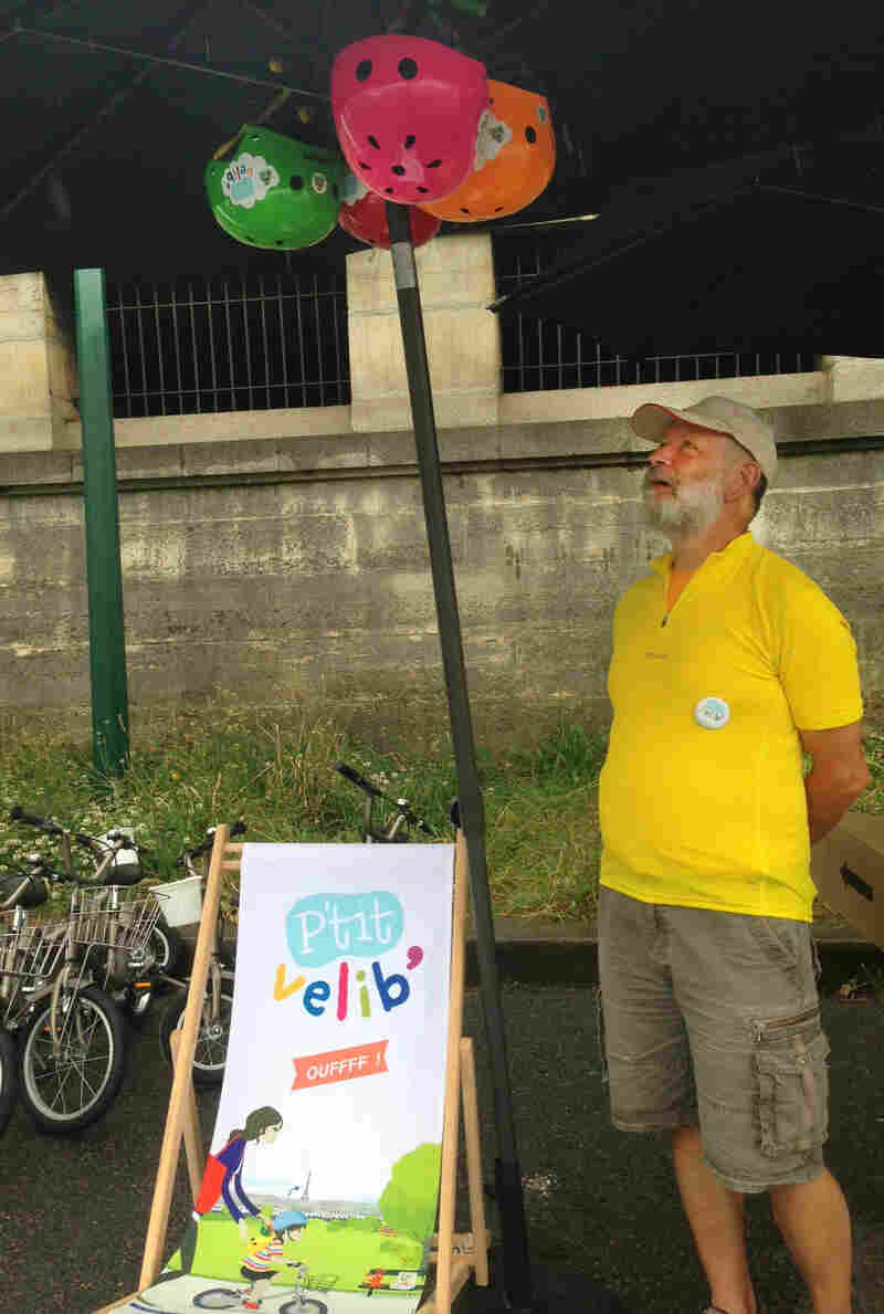 Joel Sick displays colorful helmets for rent at his P'tit Velib stand. His bikes come in four different sizes for children ages 2-8.