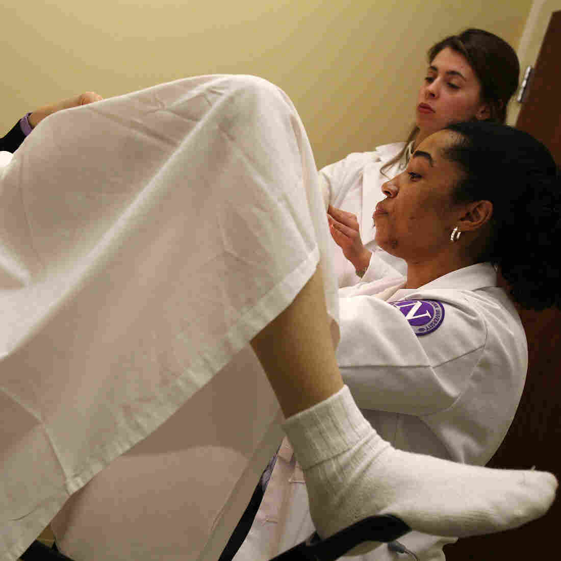 First-year medical student Michelle Gentile assists her classmate Abbie Harts as she performs a pelvic exam on a volunteer at Northwestern University.