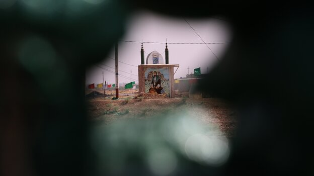 An Iraqi Turkmen fighter looks at an icon of seventh century Imam Ali bin Abi Talib, Islam's fourth caliph and cousin and son-in-law of Prophet Muhammad, in Taza Khormato, Iraq, earlier this month.