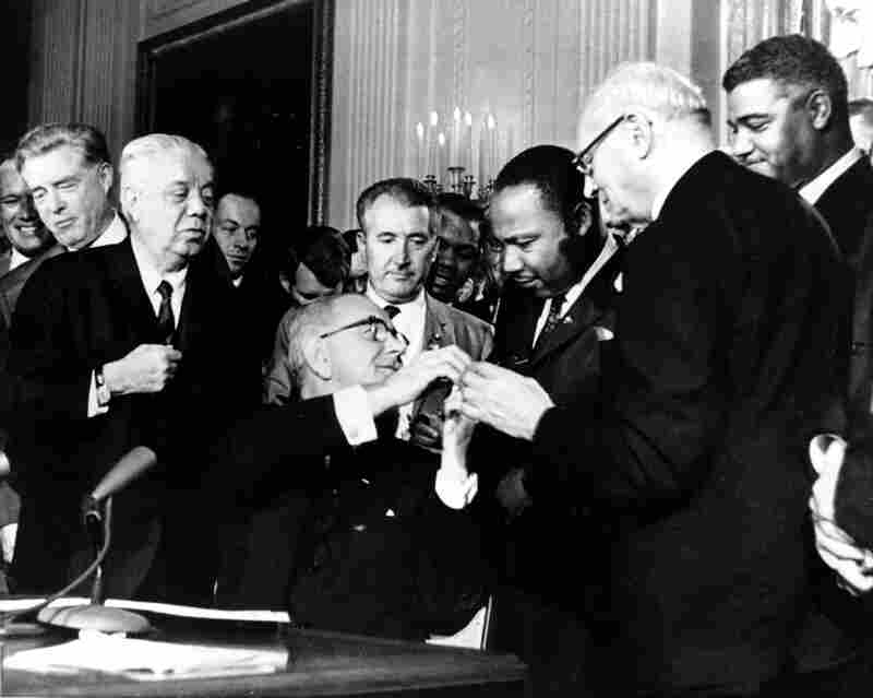 President Lyndon B. Johnson reaches to shake hands with Martin Luther King Jr. after presenting the civil rights leader with one of the 72 pens used to sign the Civil Rights Act of 1964.