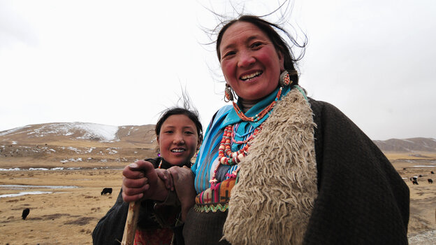 A mother and daughter herd their yaks along a highway on the Tibetan plateau.