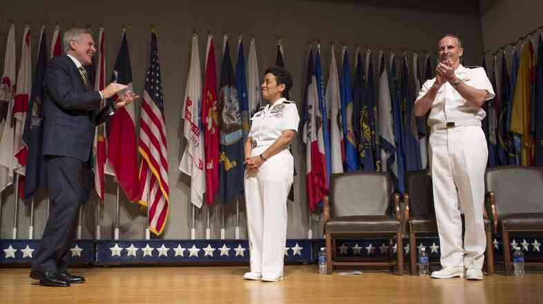Secretary of the Navy Ray Mabus and Chief of Naval Operations Adm. Jonathan Greenert applaud Adm. Michelle Howard on her promotion Tuesday.
