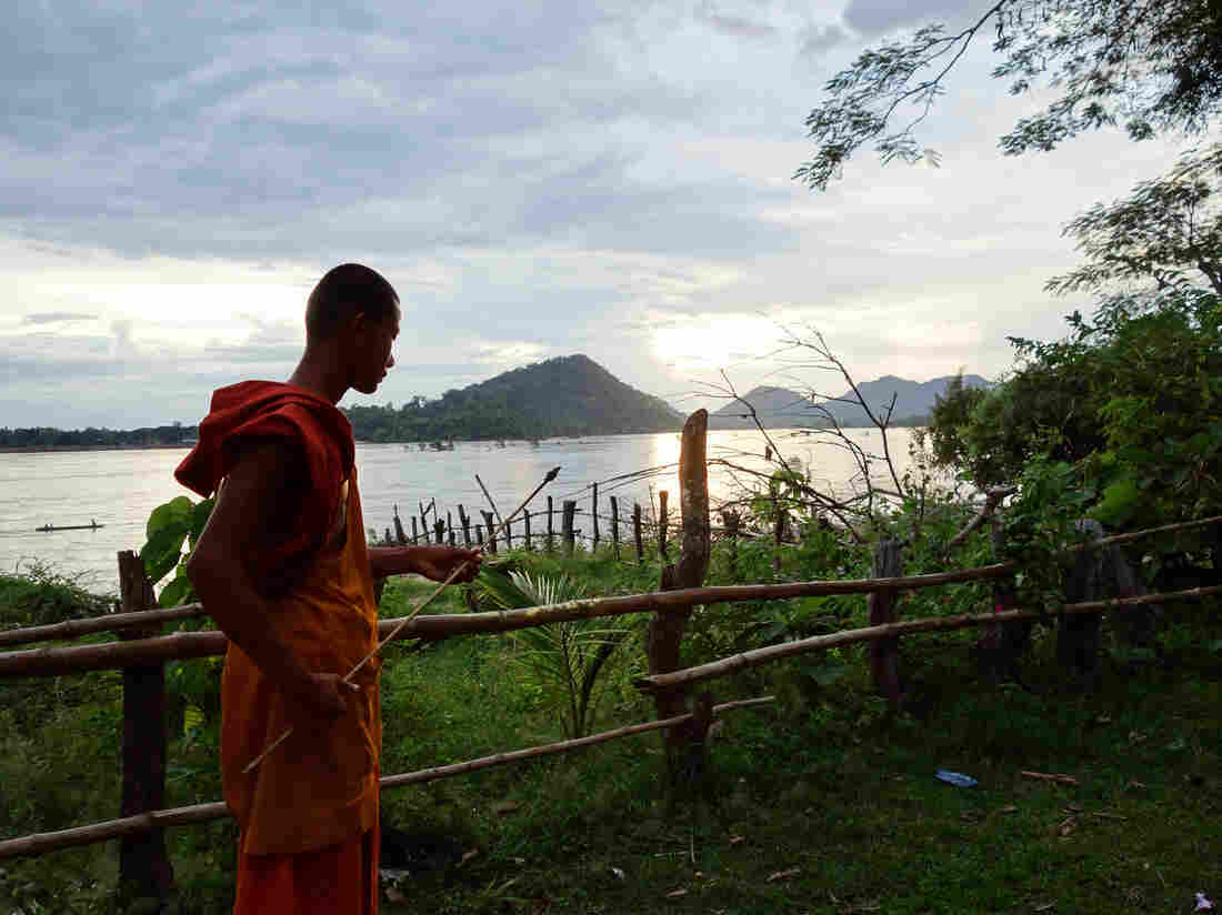 A Buddhist monk pokes at a fire on Don Sadam island.