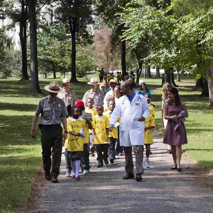 Dr. Robert Zarr, second from right, leads a hike through a park in Washington, D.C.