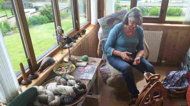 Ingrid Eunson sits at the spinning wheel in her home in the small town of Brae in Scotland's remote Shetland Islands. She knits yarn that she spins and dyes herself, traditions that her ancestors practiced for generations.
