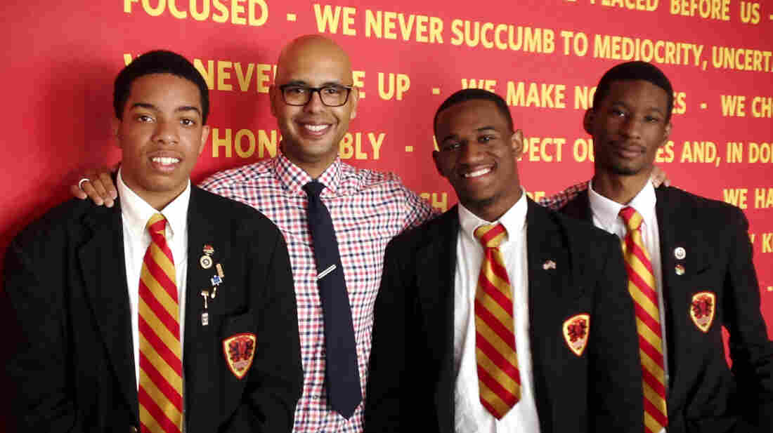 """Urban Prep founder Tim King stands in front of the school's """"We Believe"""" creed with three of the school's graduates. Steven Clark (left), 17, will attend Denison University, Dwayne Mitchell, 18, will go to the University of Illinois and Derrick Little (right), 17, will attend Georgetown University."""