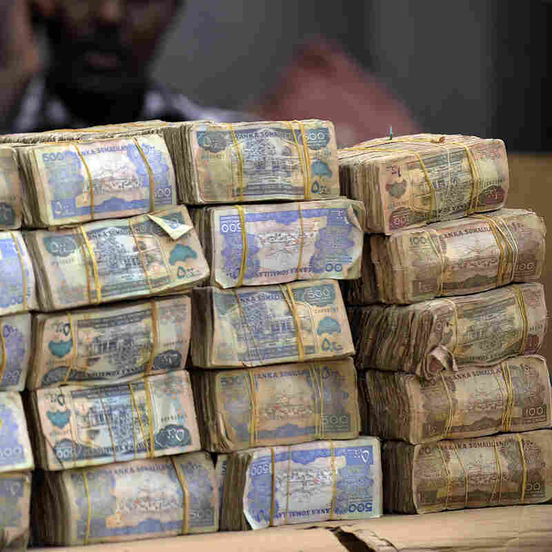 A money changer sits behind piles of banknotes in Hargeisa in Somaliland, an autonomous, relatively peaceful region in northern Somalia. The self-declared nation of Somaliland, like Somalia itself, lacks a formal banking system, and residents rely on hawaladars to receive money from abroad.