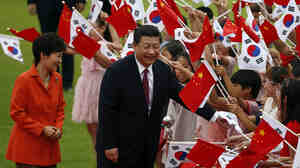 Chinese President Xi Jinping (right) and South Korean President Park Geun-hye greet children waving the two countries' national flags at the presidential Blue House in Seoul on Thursday. Xi has yet to visit North Korea.