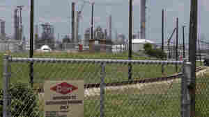 A sign posted on a roadside fence outside a Dow Chemicals plant in Freeport, Texas. The front-runner for governor, GOP Attorney General Greg Abbott, sparked controversy recently by suggesting citizens should simply go to nearby chemical and fertilizer plants and ask what's being stored there if they are worried about hazardous materials.
