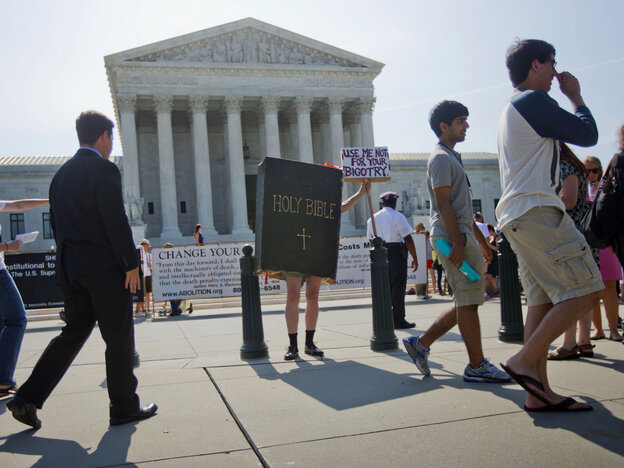 A demonstrator dressed as the Bible stands outside the Supreme Court in Washington, D.C., awaiting the court's decision on the Hobby Lobby case Monday.