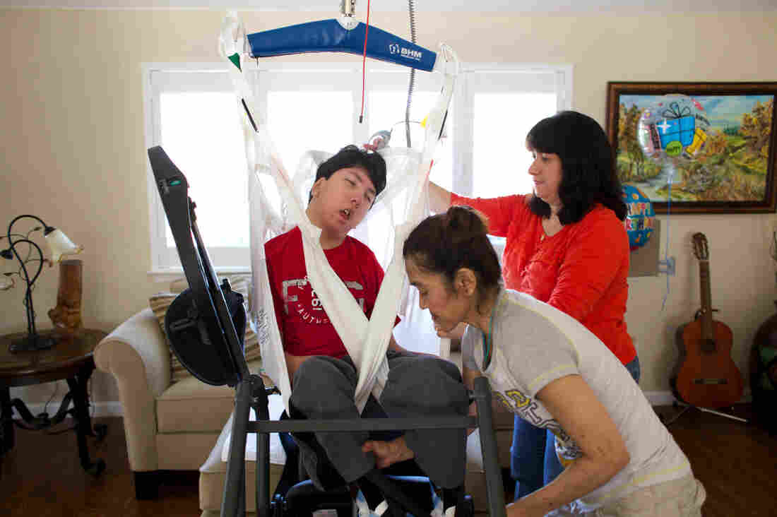 """Justin Lee is loaded into a """"stander"""" by his mother Judy (right) and his physical therapist, Rika Matsudo. The device allows Justin to be positioned upright for physical therapy."""