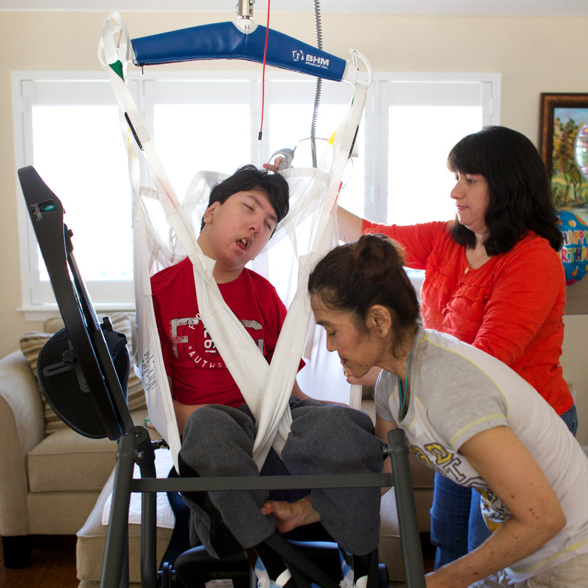 "Justin Lee is loaded into a ""stander"" by his mother Judy (right) and his physical therapist, Rika Matsudo. The device allows Justin to be positioned upright for physical therapy."