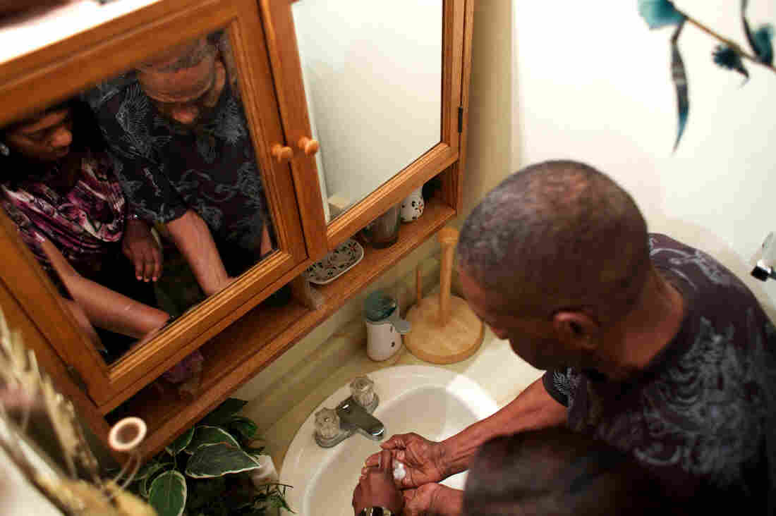 Loretta Jackson shows her father, Theodis Turner, how to wash his hands. Theodis has dementia and lives with the Jacksons.