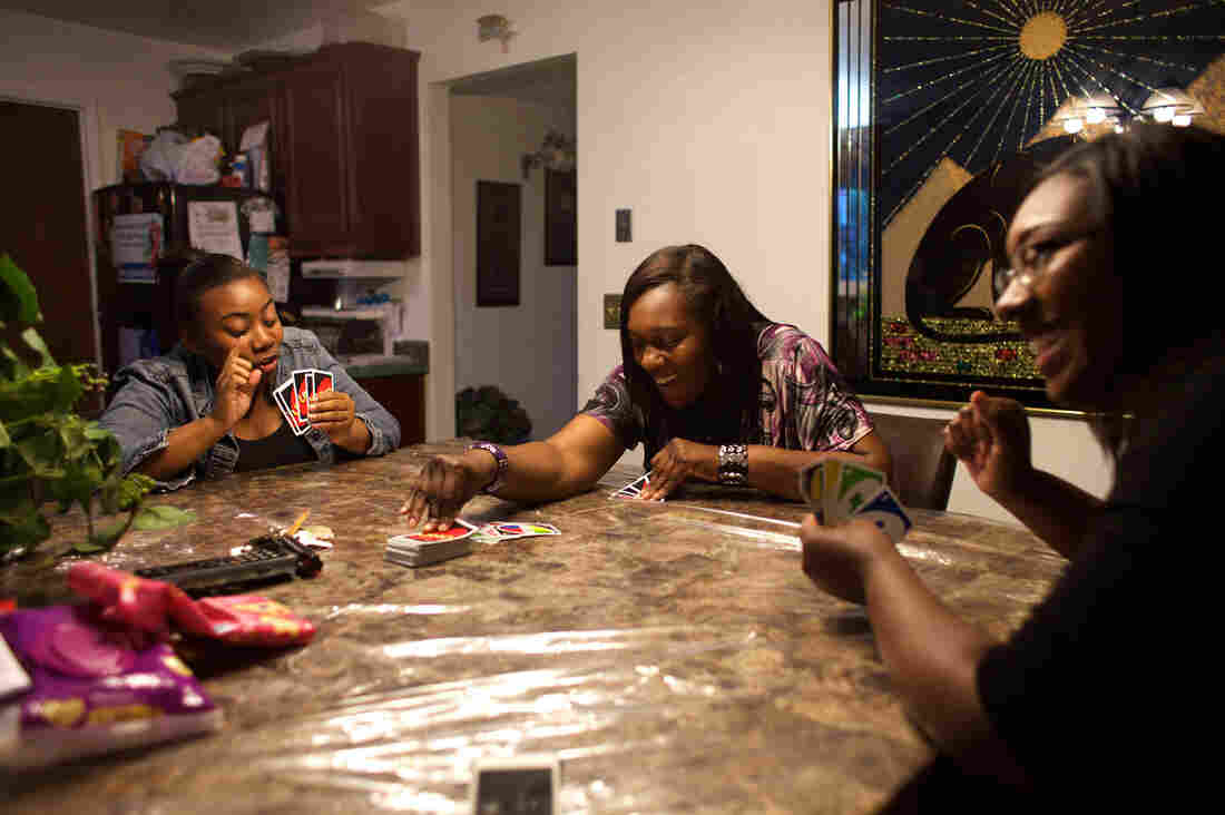 Loretta Jackson (center) plays a card game with her daughters Onasha Mitchell and Johkida Jackson on a Friday evening at home.