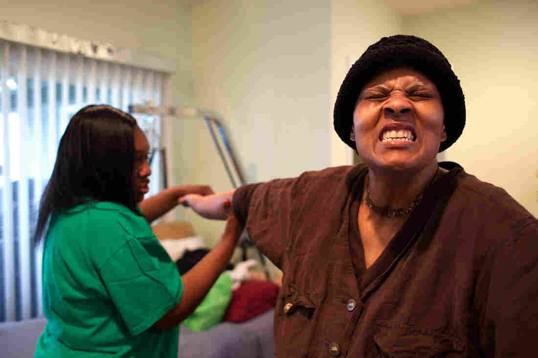 Loretta Jackson gently stretches the hands of her sister, Shirlene English, to aid physical rehabilitation after Shirlene's brain aneurysm and stroke.