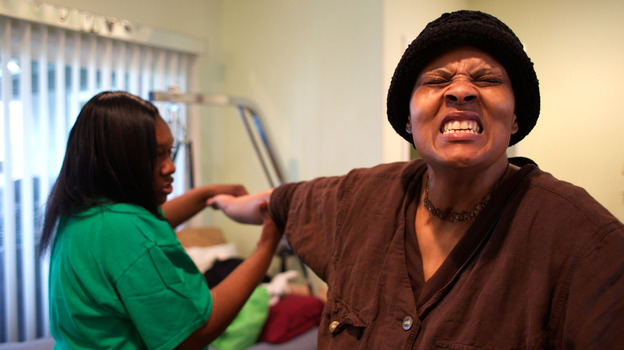 Loretta Jackson gently stretches the hands of her sister, Shirlene English, to aid physical rehabilitation after Shirlene's brain aneurysm and stroke. (Andrew Nixon/Capital Public Radio)