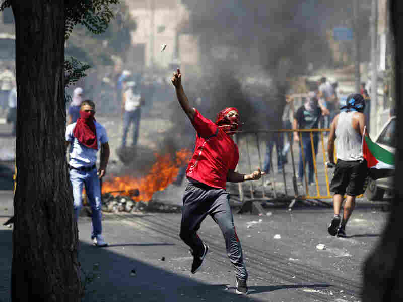 A Palestinian throws a stone during clashes with Israeli police after prayers on the first Friday of the holy month of Ramadan in East Jerusalem on Friday. The clashes came ahead of the funeral of a slain Palestinian teenager.
