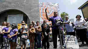 Human-rights activist Enrique Morones, at podium, speaks during a rally in support of immigrants on Wednesday in San Diego. A group of about 70 people rallied in support of migrant children and families Wednesday, a day after U.S. Homeland Security b