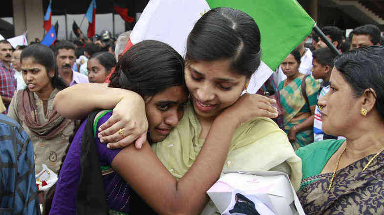 An Indian nurse caught up in fighting in Iraq hugs her sister after arriving at the airport in the southern Indian city of Kochi on Saturday.
