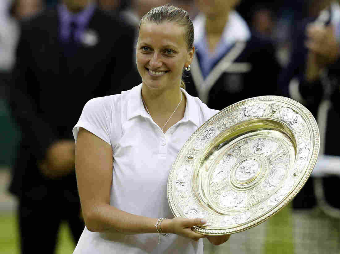 Petra Kvitova of the Czech Republic holds the Venus Rosewater Dish trophy after defeating Eugenie Bouchard of Canada in their women's singles final tennis match at the Wimbledon.