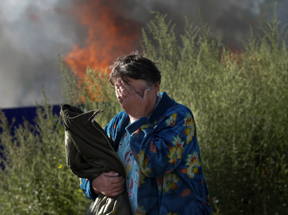 A woman cries near her burning house after shelling in the city of Slovyansk, Donetsk Region, eastern Ukraine, last month. The city of 100,000 has now been retaken from pro-Russian separatists. (Dmitry Lovetsky/AP)