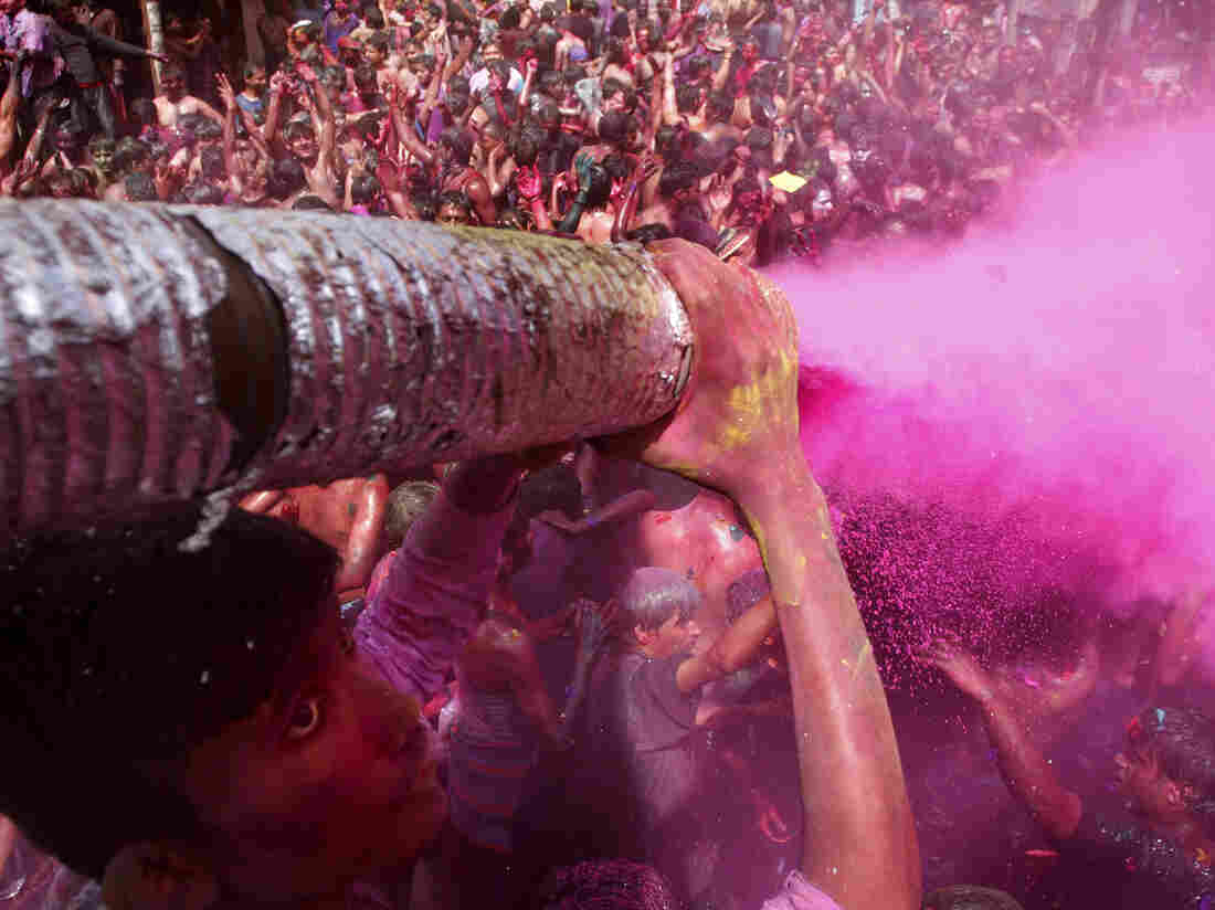 A man sprays colored dye on people dancing during Holi celebrations in India in 2012. Holi, the Hindu festival of colors, also heralds the coming of spring — a detail that partiers at the Shout Color Throw might miss.