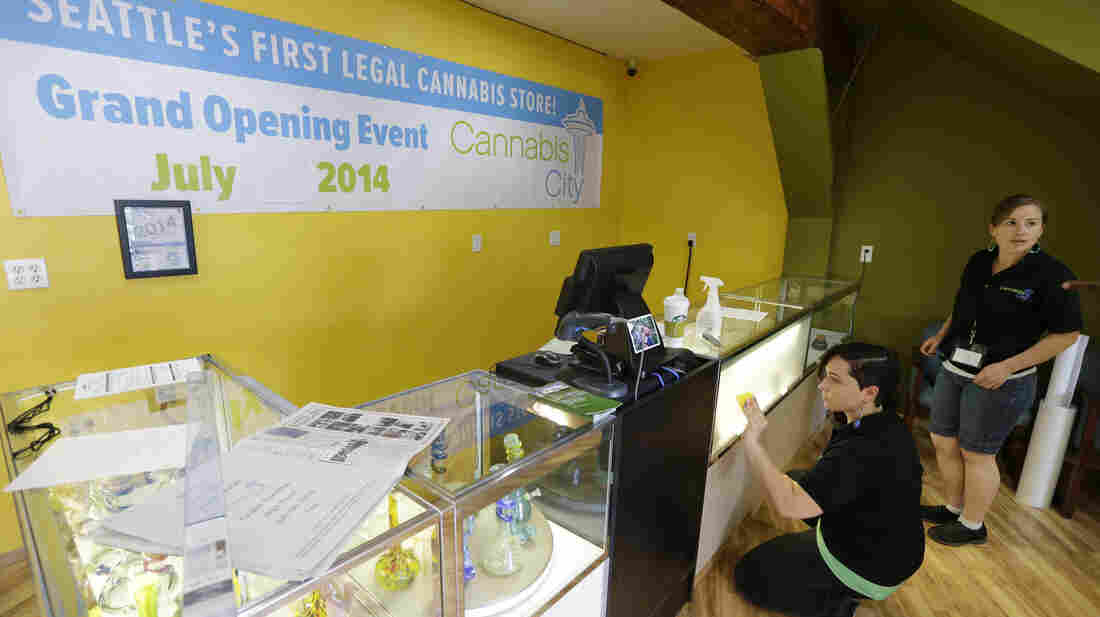 Amber McGowan, left, and Krystal Klacsan work Monday at Cannabis City in Seattle, a day before the store is to begin legal pot sales on Tuesday. The store will be for now the only one in Seattle to sell recreational marijuana.