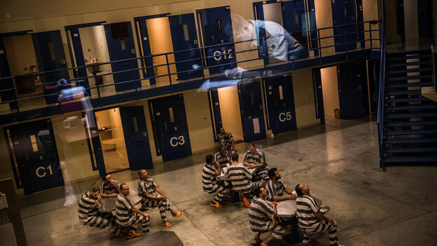 An officer is reflected in the glass as inmates sit in the Williston, N.D., county jail in July 2013.