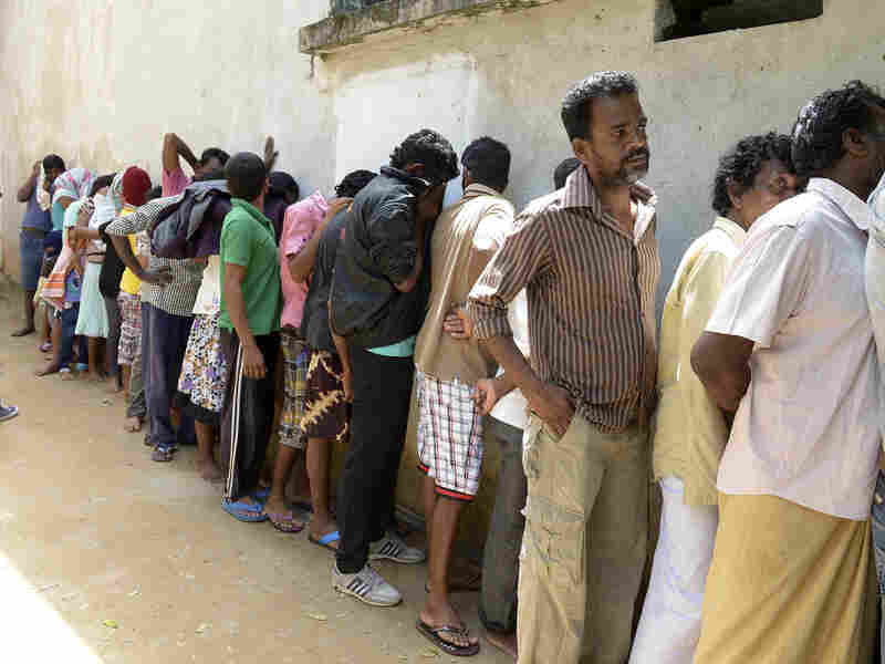 Sri Lankan asylum seekers who were sent back by Australia cover their faces as they wait to enter a magistrate's court in Galle, Sri Lanka, on Tuesday.
