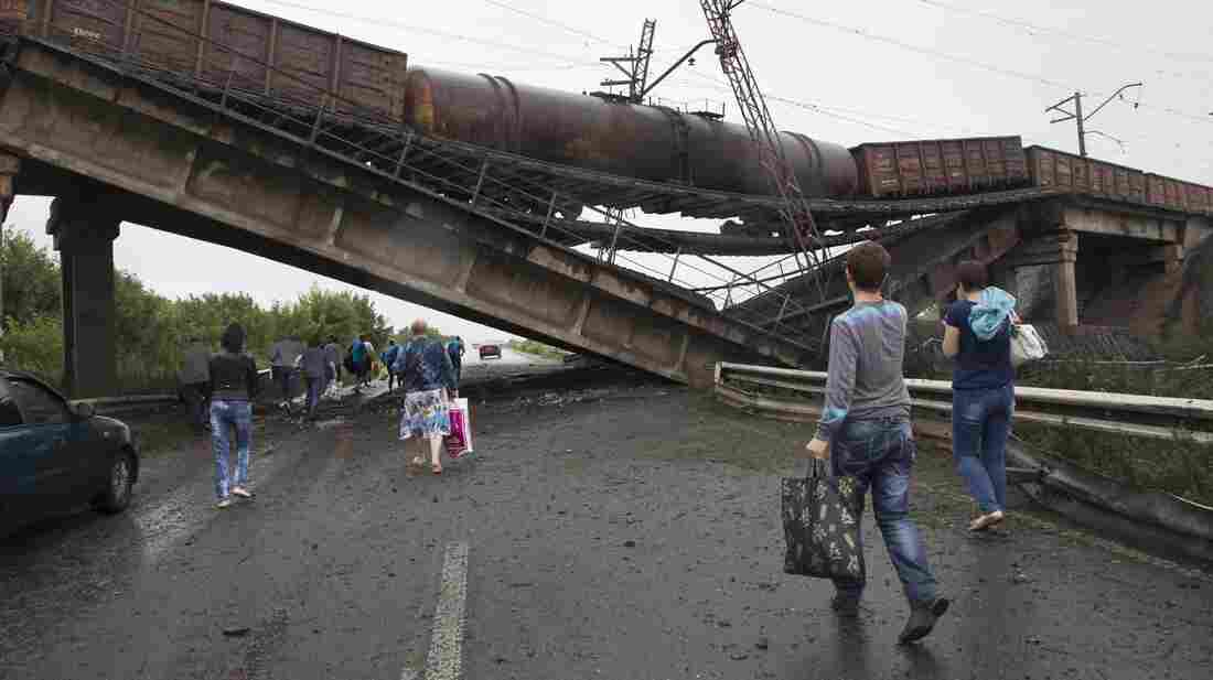 People walk under a destroyed railroad bridge over a main road leading into the city of Donetsk in eastern Ukraine Monday. Kiev is calling on pro-Russian militants to disarm before holding peace talks.