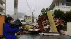 A reporter stands next to a wooden house and restaurant that collapsed across a street due to strong winds from Typhoon Neoguri, in Naha city on the island of Okinawa on Tuesday.