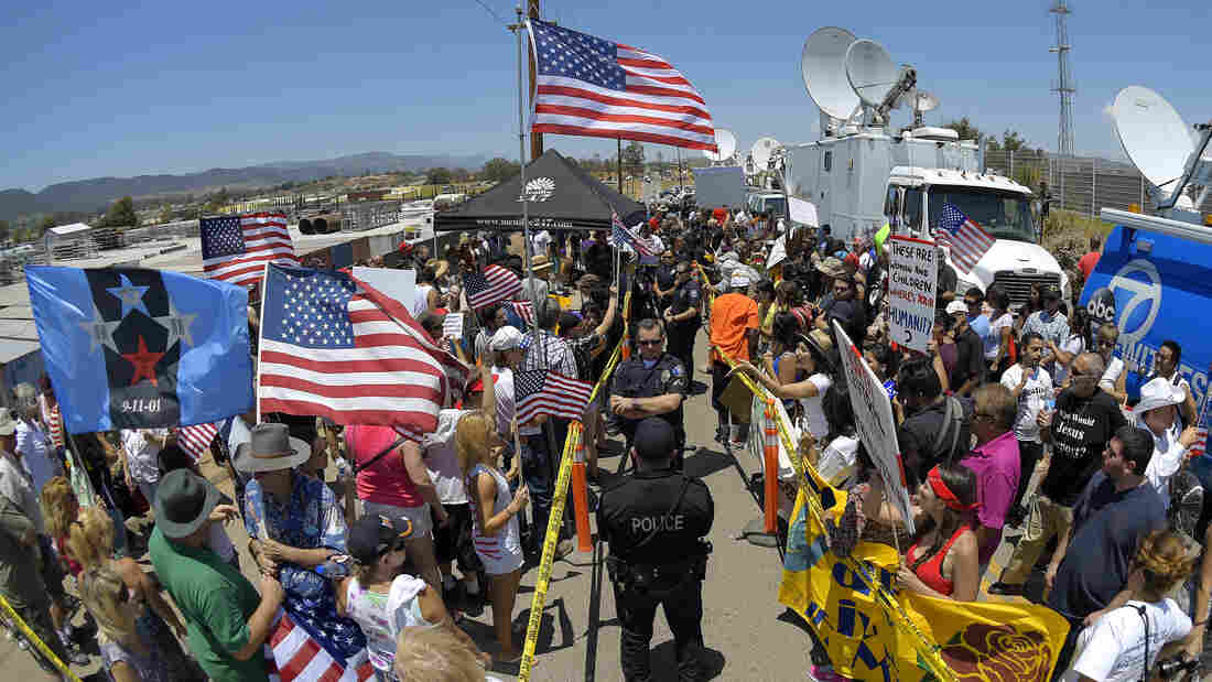Demonstrators from opposing sides confront each other while being separated by police officers on July 4, outside a U.S. Border Patrol station in Murrieta, Calif.