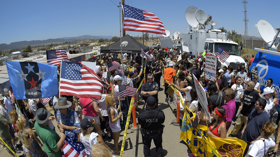 Demonstrators from opposing sides confront each other while being separated by police officers on July 4, outside a U.S. Border Patrol station in Murrieta, Calif. (Mark J. Terrill/AP)