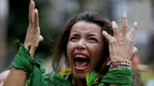 A fan screams as she watches Brazil lose to Germany, in a live telecast Tuesday in Belo Horizonte, Brazil. The host nation is reeling from its loss in the World Cup semifinal.