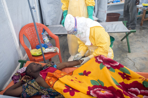 Medical workers with the nonprofit Doctors Without Borders treat a patient for Ebola in Gueckedou, Guinea. Despite their protective gear, the workers try to maintain human contact with patients by talking with them and getting close enough to look into their eyes.