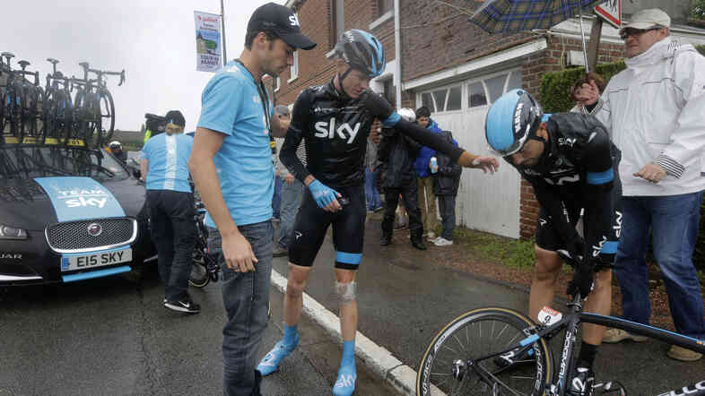 Britain's Chris Froome gestures to a teammate (right) after getting up from his third crash in two days. Froome, who hurt his wrist in Tuesday's fall, has abandoned the race that he won in 2013.