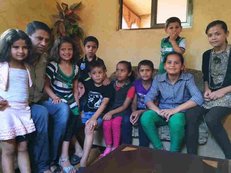 Abdel Kareem Shamali, shown with his children and nieces, tries to reassure the kids by acting like the bombs don't bother him.