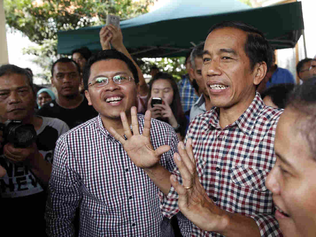 """Indonesian presidential candidate Joko """"Jokowi"""" Widodo (center) holds a news conference Thursday in Jakarta. """"Quick counts"""" of the election results give Widodo a narrow lead over his rival."""