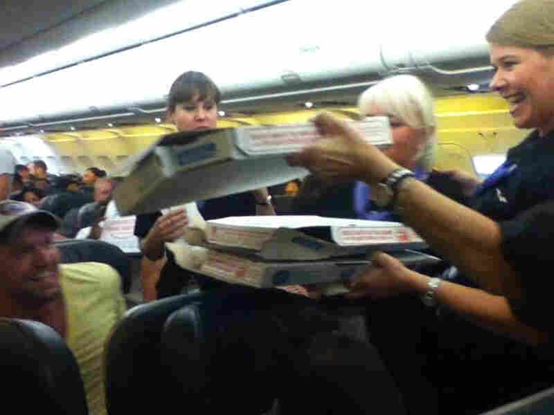 Intrepid pizza purveyors in action: Frontier Airlines flight attendants pass out pies to the delighted passengers.