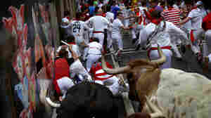 Revelers try to keep ahead of the horns during a running of the bulls Thursday at the San Fermin festival in Pamplona, Spain.