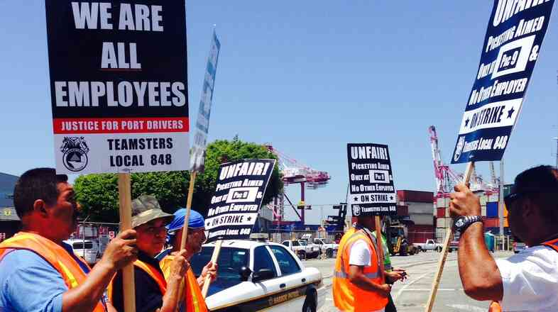 Picketers supporting independent truck drivers at the ports of Los Angeles and Long Beach stand outside a container terminal.