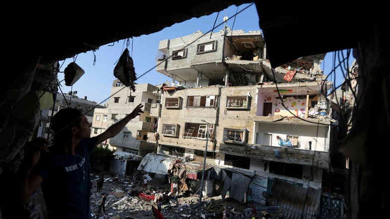 Palestinians inspect the rubble of a house hit by an Israeli missile strike in Gaza City on Thursday. Israel escalated its aerial assaults on Gaza on Thursday, with Prime Minister Benjamin Netanyahu saying there are no plans for a cease-fire.
