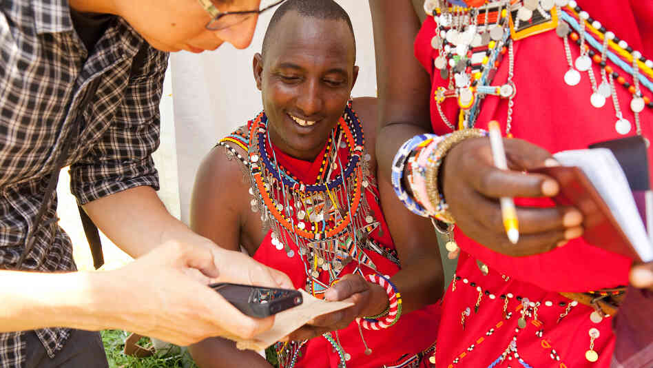 Philip Kisaikae and another Maasai warrior swap email addresses with Juan Carlos Vera, who attended this summer's Smithsonian Folklife Festival.